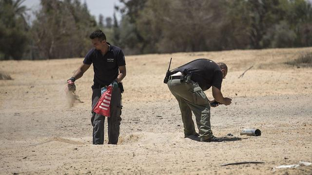 Police sappers collect shrapnel of a rocket launched from Gaza  (Photo: EPA)