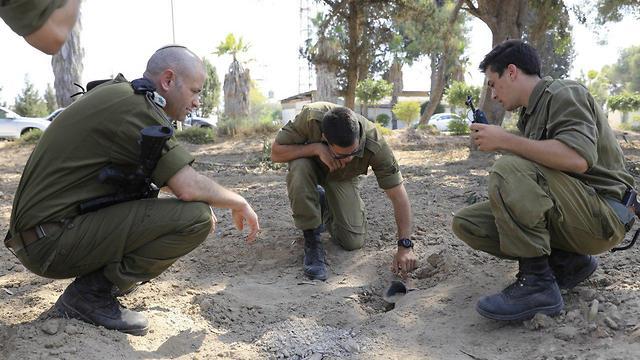 חיילים בודקים נזק שנגרם לכביש בעוטף עזה (צילום: AP)