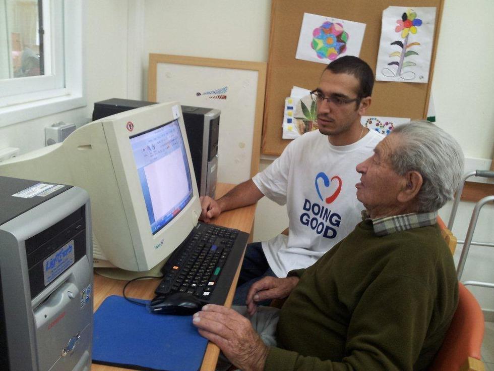 צעיר ומבוגר יושבים יחד מול מחשב ()
