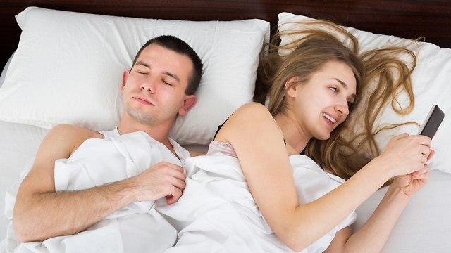 זוג במיטה לאורו של הסמארטפון (צילום: Shutterstock)