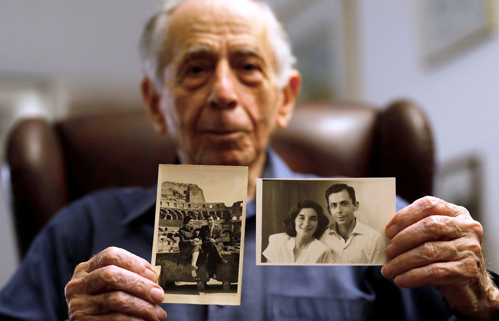 Shlomo Hillel, 95, a former Israeli diplomat and minister, holds photos of him and his late wife Suzanna Rosner (Photo: Reuters)