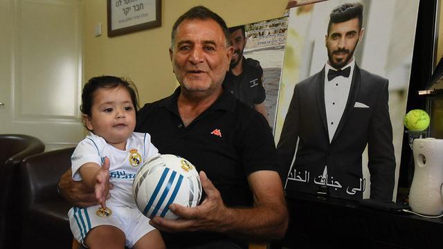 Afif Satawi holding his grandson (Photo: Avihu Shapiro)