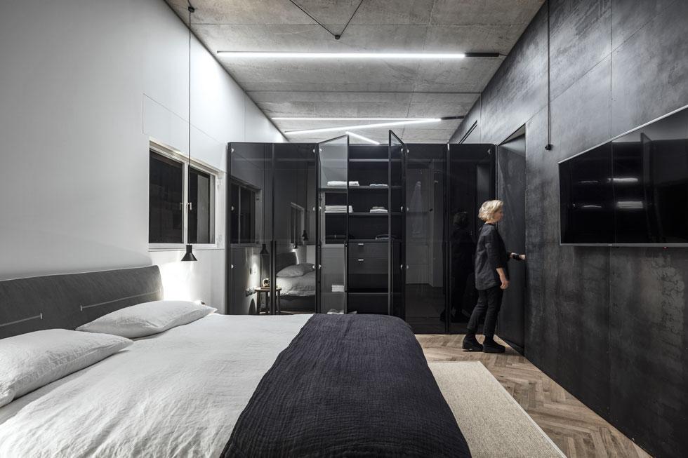 בין שני חדרי השינה מפריד ארון דו-צדדי שלא מגיע לתקרה. מחיצת זכוכית שמשלימה את המרווח מאפשרת פרטיות אך מונעת תחושה של חדר אטום  (צילום: עמית גרון)