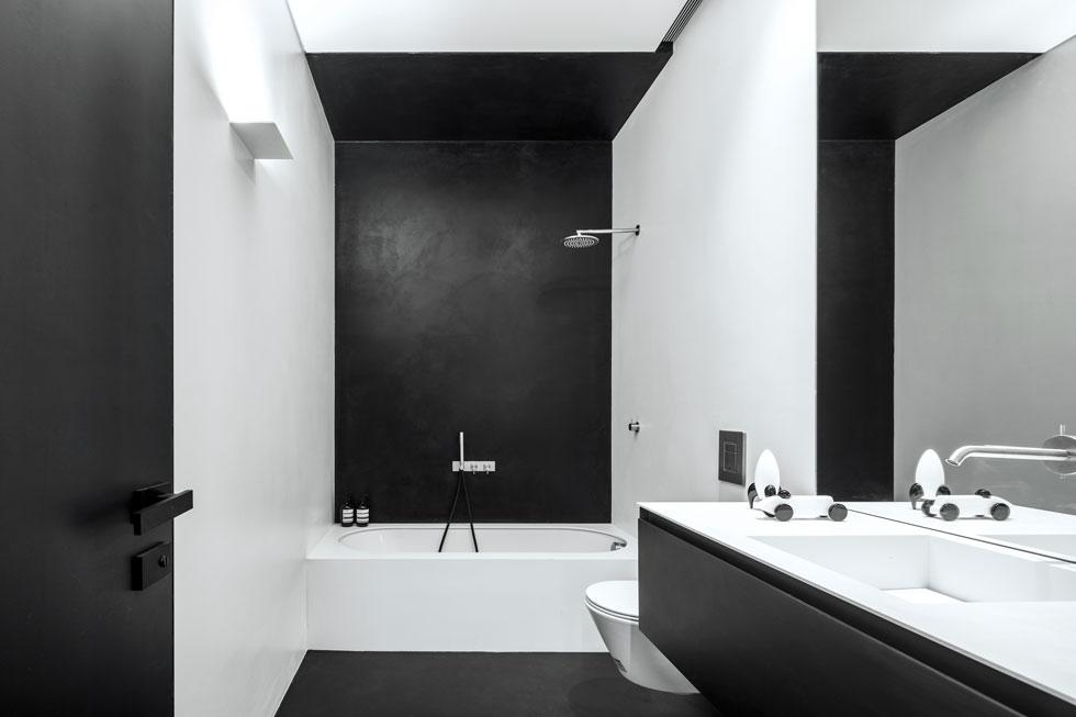 """חדר הרחצה הקטן יותר, הצמוד לחדר האורחים. שניהם עוצבו בשחור-לבן, עם קירות שחופו ברזינה (חומר צמנטי עמיד בפני מים). """"העובדה שהבניין עבר מהפך"""", אומרת האדריכלית אירית אקסלרוד, """"נתנה לי את הגושפנקא להכניס לכאן משהו שהוא לא באוהאוס"""" (צילום: עמית גרון)"""