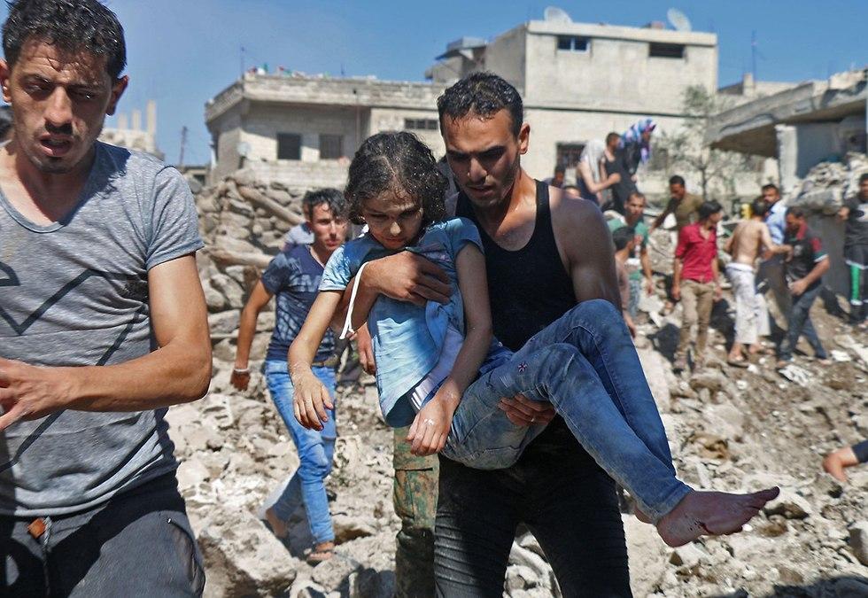 פינוי ילדה שנפצעה הפצצות של צבא אסד ב דרעא דרום סוריה (צילום: AFP)