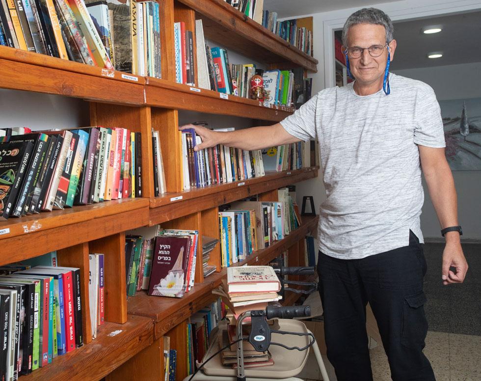 """גידי צור בספרייה שמפעילה העמותה שבראשותו בקיבוץ לוחמי הגטאות. """"העובדה שילדיי בחרו בחינוך אומרת שהדברים חלחלו והשפיעו"""" (צילום: גיל נחשותן)"""