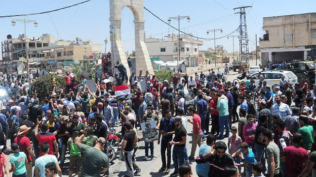 תושבי העיירה דאעל מחוז דרעא דרום סוריה חוגגים את כניסת הצבא לעיירה (צילום: רויטרס)