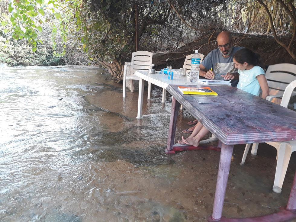 עופרי ואלי מכינים שיעורי בית במתמטיקה בתוך הנחל, ליד האמפי (צילום: אירית נצר קאופמן)
