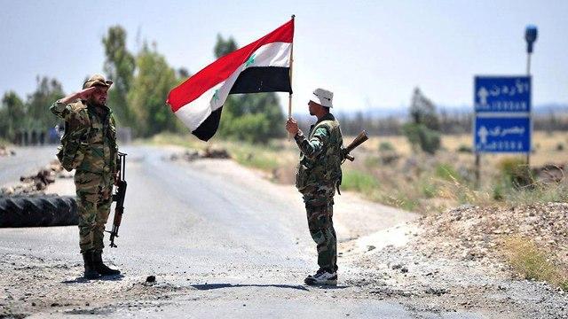 חייל סורי מצדיע לדגל סוריה  (צילום: AFP)