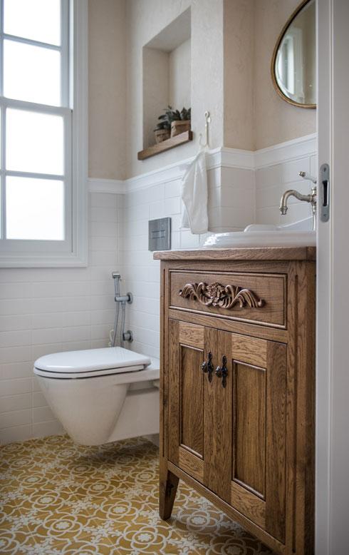 ארון כיור מעץ וריצוף מעוטר בגווני חרדל בשירותי האורחים (צילום: גלעד רדט)