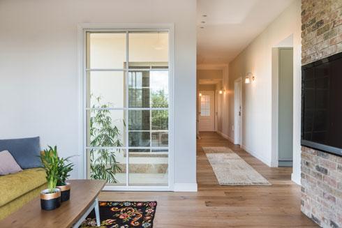 פינת המשפחה בקומה השנייה מוארת בחלון שממנו נשקף הפטיו (צילום: גלעד רדט)