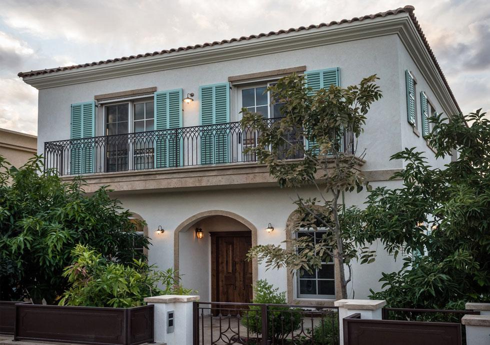 חזית הבית: לדלת הכניסה ולחלונות בקומה התחתונה מסגרות מקושתות מאבן כורכר. תריסי הטורקיז בקומה השנייה מוסיפים צבע  (צילום: גלעד רדט)