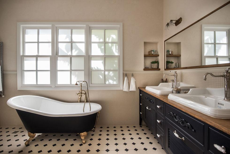 חדר הרחצה של ההורים רוצף בשחור-לבן, והאמבטיה השחורה ניצבת על רגליים זהובות מתחת לחלון (צילום: גלעד רדט)