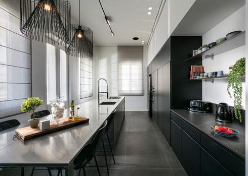 קיר הארונות במטבח משמש גם לאחסון כללי והופך בחלקו לפינת קפה פתוחה (צילום: אלעד גונן)