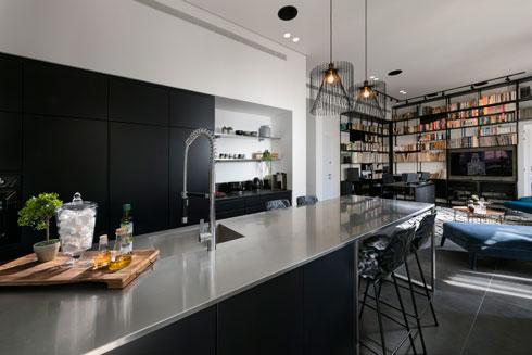מעל האי במטבח תלויות מנורות מחוטי ברזל עדינים, שהן התאורה הדקורטיבית היחידה בדירה (צילום: אלעד גונן)