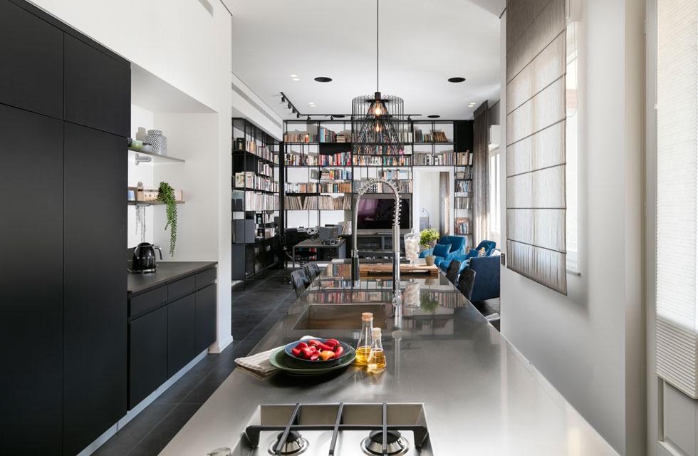 """מבט מהמטבח הארוך והצר אל הסלון ופינת העבודה. """"לדירה היה מהתחלה את האופי שלה"""", אומרת האדריכלית, """"ואי אפשר היה  להתעלם מזה""""  (צילום: אלעד גונן)"""