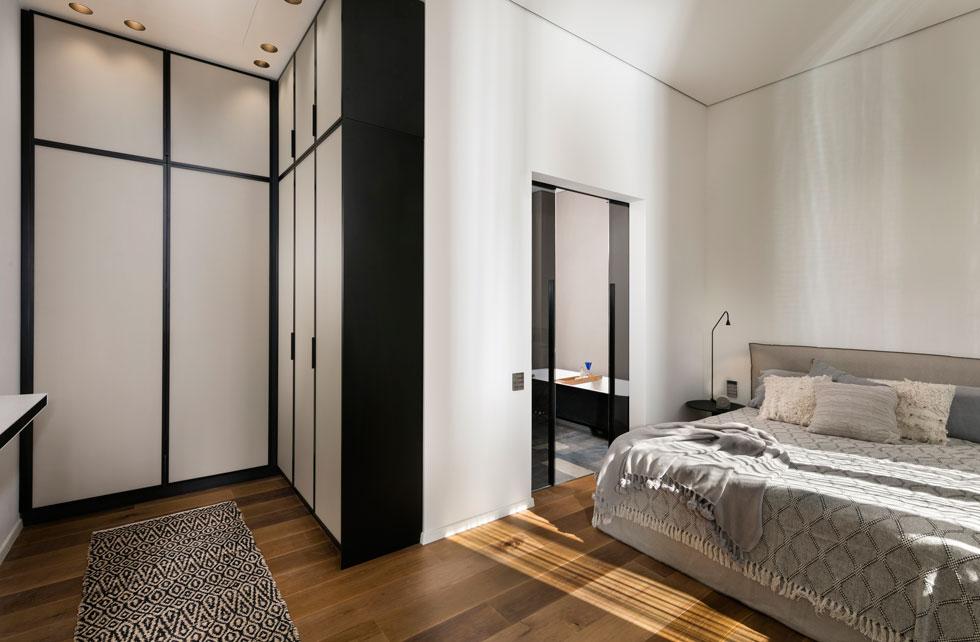 בכניסה לחדר השינה חדר ארונות פתוח, ובין המיטה המרופדת לחדר הרחצה הצמוד מפרידות דלתות הזזה מזכוכית שחורה (צילום: אלעד גונן)