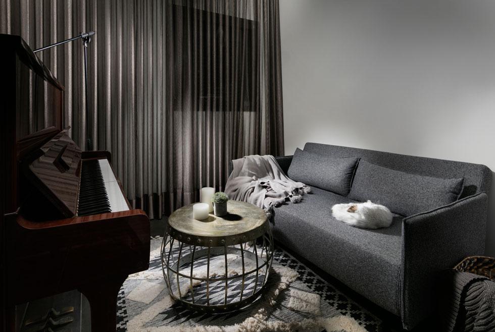 """הממ""""ד משמש כחדר אורחים וכמקום משכנו של הפסנתר. גם כאן נמשכת פלטת הגוונים האופיינית לדירה, בגוני אפור חם ונחושת  (צילום: אלעד גונן)"""