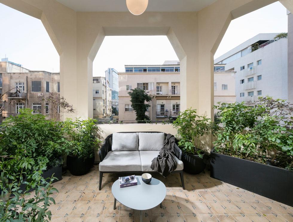 צמחים מטפסים באדניות שחורות ופינת ישיבה במרפסת הפתוחה הפונה לרחוב מעניקים אווירה של גאזיבו בנוי בלב העיר (צילום: אלעד גונן)