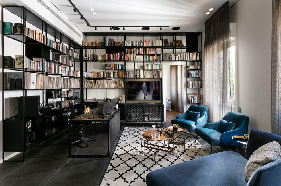 את החלל המרכזי בדירה מגדירה ספריית ברזל שחורה המטיילת, מרצפה עד תקרה, על שני קירות, ומקיפה את דלת הכניסה לחדר השינה. זהו חדר עבודה והקלטות, ופינת הישיבה הסלונית פונה אל שולחן העבודה (צילום: אלעד גונן)