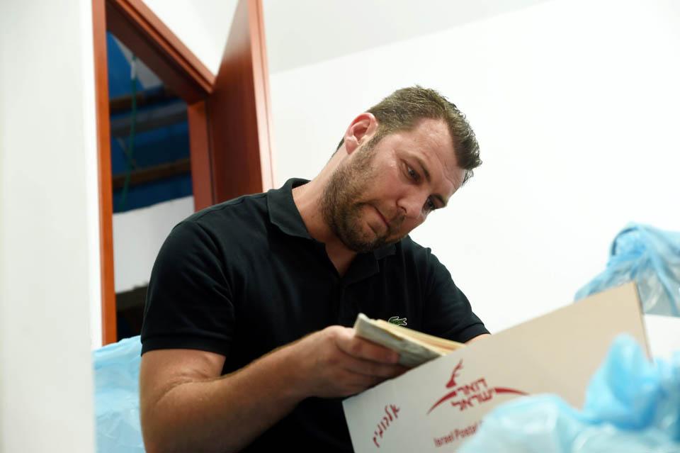 Сын разбирает бумаги отца. Фото: Хаим Оренштейн