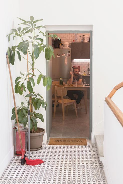 זוהר, הדייר הראשון בבית, יושב במטבח המרווח בדירה (צילום: עמרי טלמור)