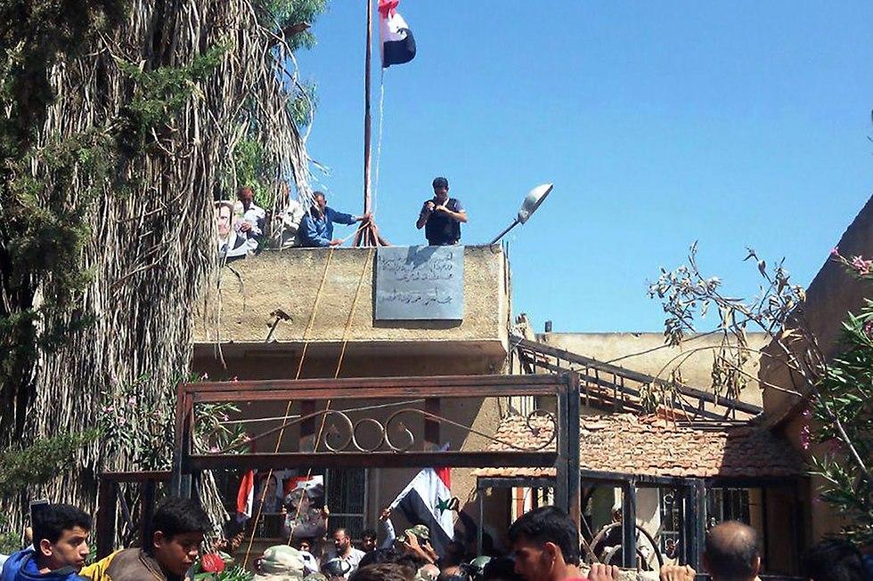 דגלי סוריה בדרעא (צילום: AFP)
