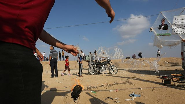 Palestinian rioter holding incendiary device attached to a kite (Photo: AFP)