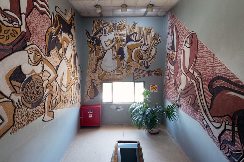 זוג האמנים מרדכי ומרים גומפל יצרו את ציור הקיר המרהיב ''ואספת דגנך'', הכובש את כל הקירות סביב גרם המדרגות המוביל אל המשרדים (צילום: גדעון לוין)