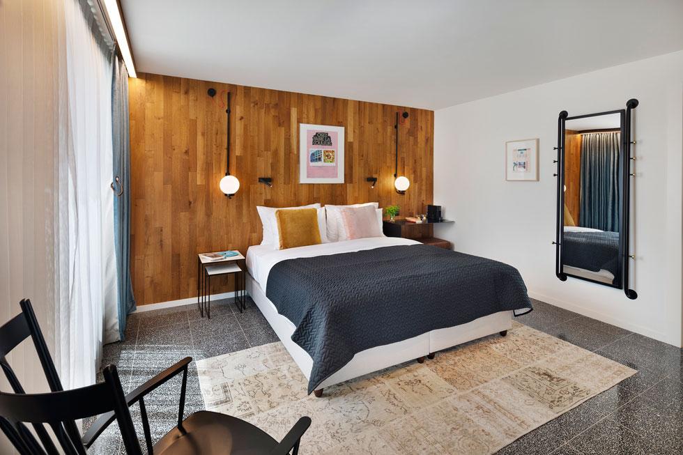 """אחד מ-43 החדרים, עם אריחי טראצו שחורים וקיר שכוסה בעץ בגב המיטה. ''רצינו לעשות בקתה אורבנית"""", אומר מיכאל חי, מומחה למלונאות (צילום: אסף פינצ'וק)"""