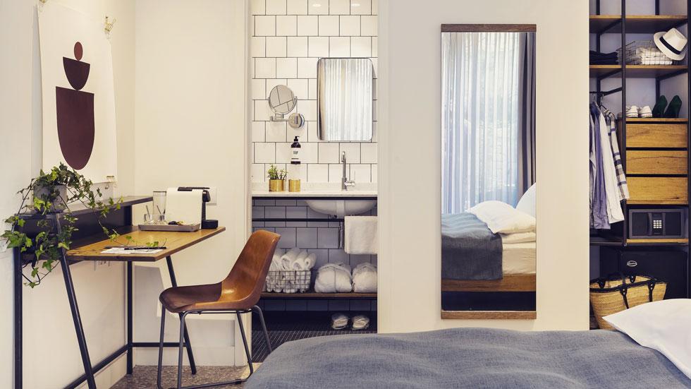 החדרים קטנים, בהירים וצנועים באופן יחסי, עם אריחי טראצו אפורים וריהוט בסיסי: מיטה, שולחן כתיבה וארון קטן עשויים ברזל ועץ, בעיצוב האדריכל (צילום: בועז לביא)