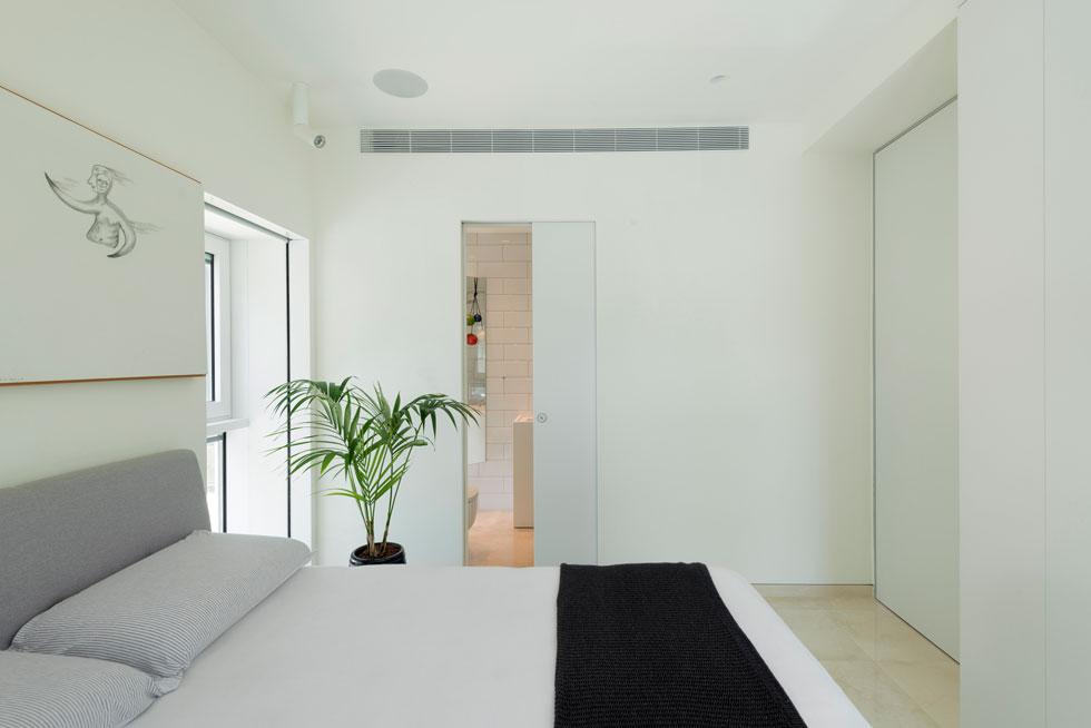 חדר השינה נהנה משפע של אור טבעי הודות לחלונות ההיקפיים הגדולים. את רוב שטחו תופסת המיטה הזוגית. ארון הבגדים המרכזי נמצא בסלון. חדר הרחצה הצמוד מופרד בדלת הזזה  (צילום: גדעון לוין)