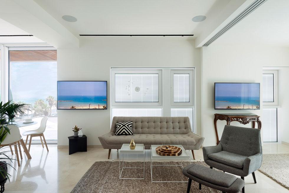 """מסכי הטלוויזיה בתוך הדירה משדרים את נוף הים המשתנה. """"ככה אני יכול לראות את הים מכל מקום"""", מספר בעל הבית, """"זה כמו תמונה אינטראקטיבית שמשתנה במהלך היום""""  (צילום: גדעון לוין)"""
