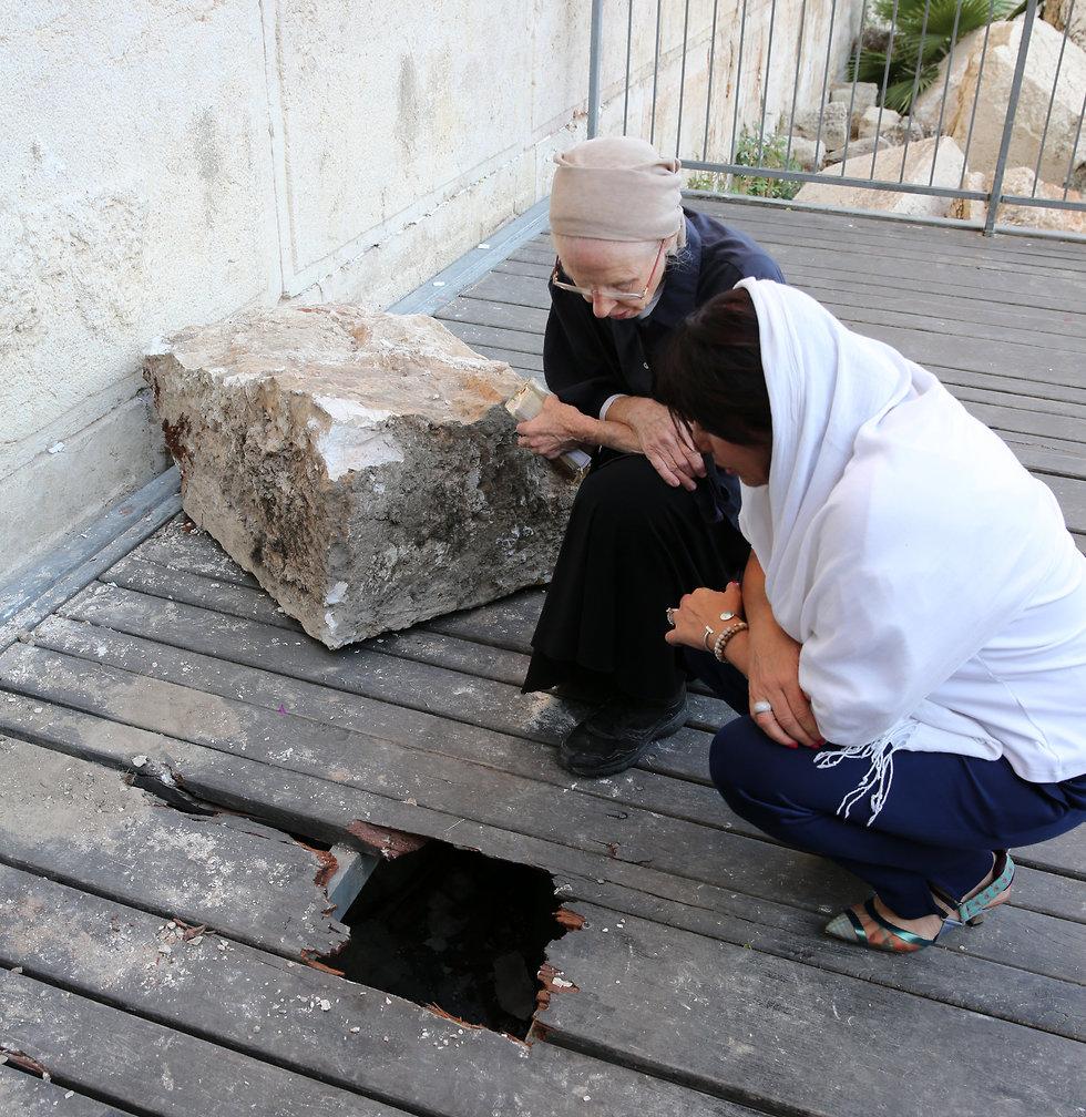 דניאלה גולדברג והשרה מירי רגב מתפללות בנקודה שבה נפלה האבן (צילום: אלכס קולומויסקי)