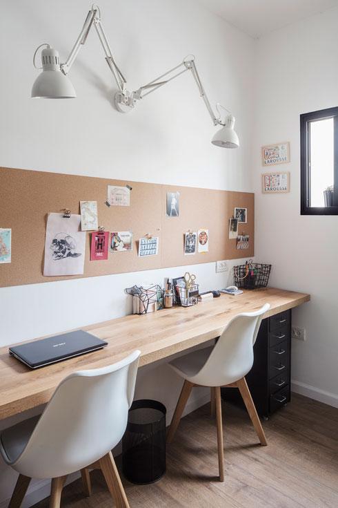 בחדר העבודה שולחן זוגי: משטח עץ אלון על רגלי מתכת, שעם על הקיר ומנורה שמתפצלת לשתיים (צילום: אביעד בר נס)