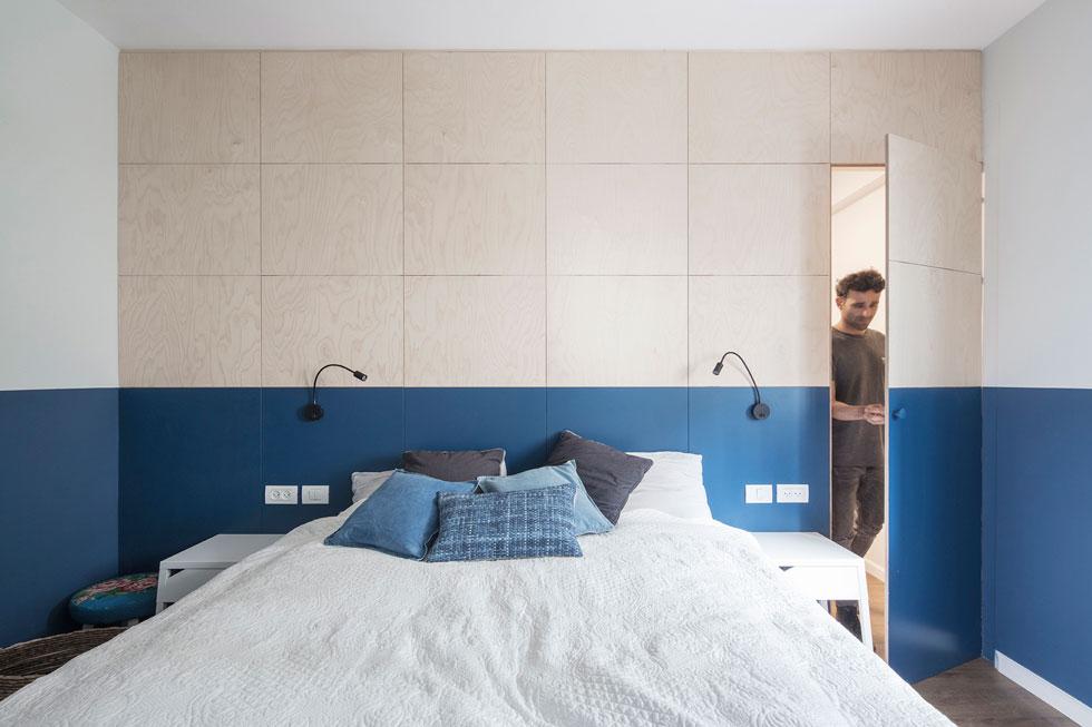 הקיר המרכזי בחדר השינה כוסה עץ בגריד ריבועי. חלקו התחתון נצבע בכחול, כגב למיטה. דלת אינטגרלית בחיפוי הקיר מובילה לחדר הארונות (צילום: אביעד בר נס)
