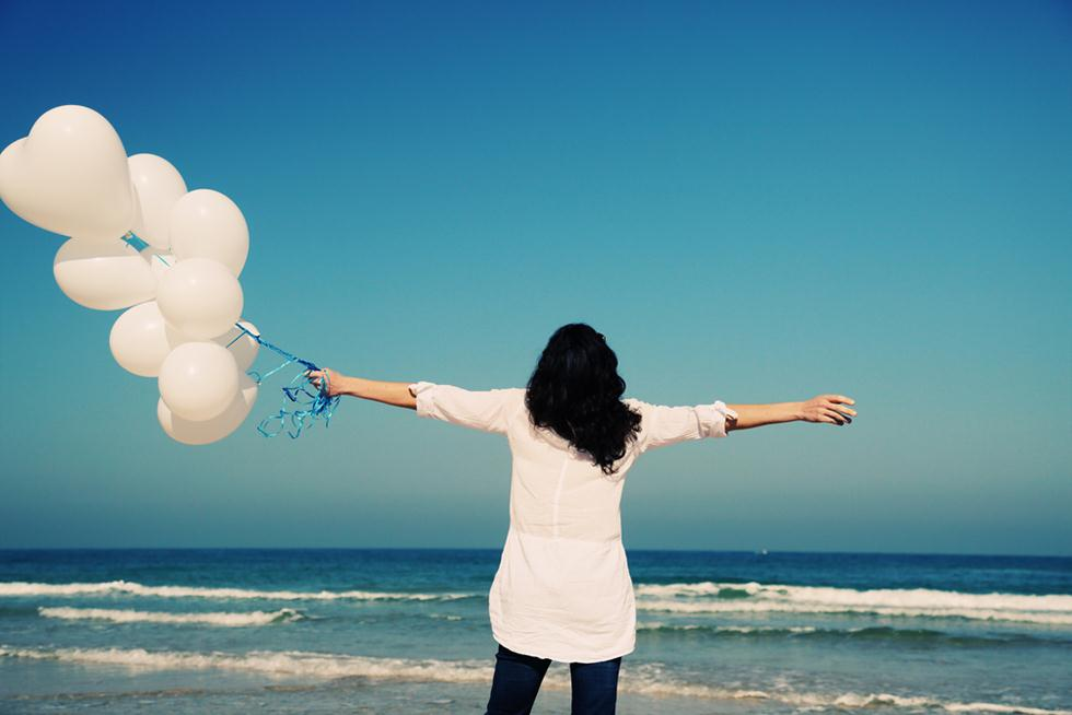 אישה עם בלונים בחוף הים (צילום: shutterstock)