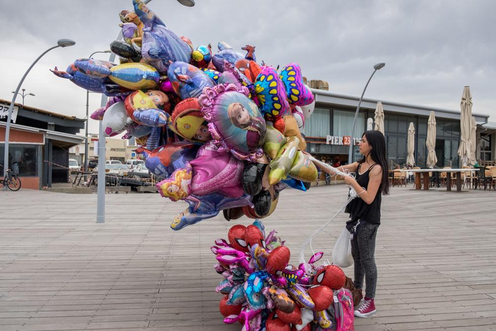 אישה עם בלוני הליום בנמל ת