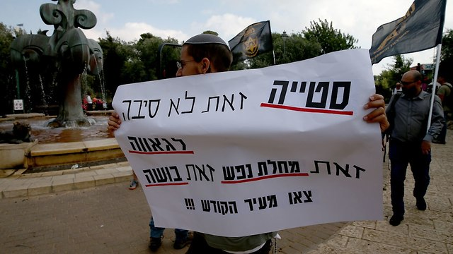 Protester against the Pride Parade holding sign saying: 'Perversion is no reason for pride, it is a mental illness, it is a disgrace, get out of the holy city!!!' (Photo: Ohad Zwigenberg)