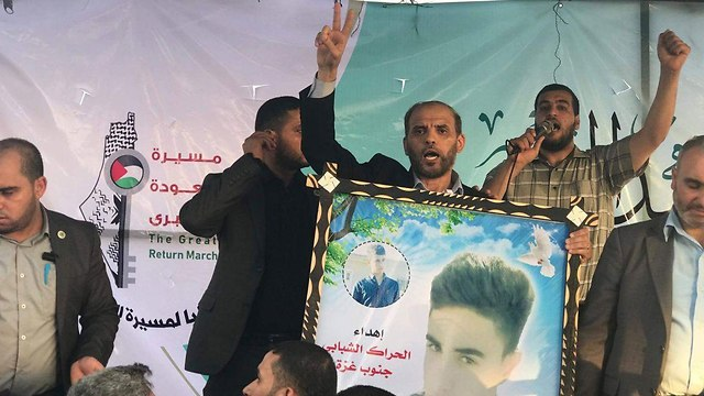 Hamas's spokesman holding a picture of a terrorist