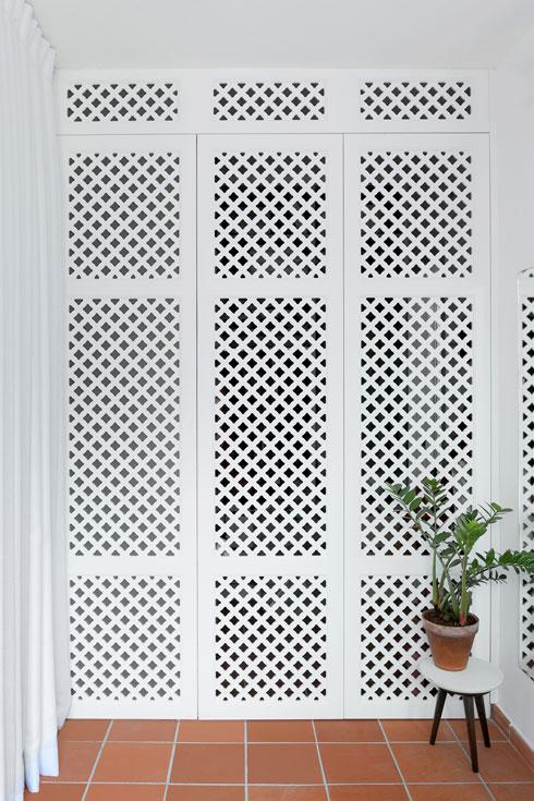מחיצה דמויית משרביה מעץ צבוע לבן מפרידה בין אזור השינה לאזור הרחצה וחדר הארונות (צילום: גדעון לוין)