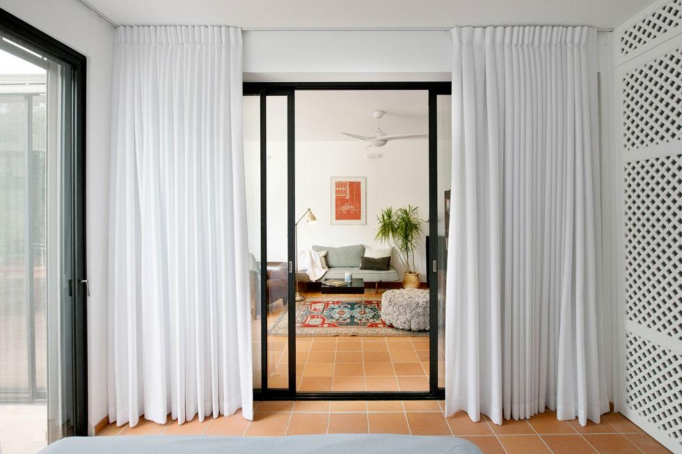 בתוך חדר השינה יצר קנטי מחיצה קלה בהשראת משרבייה, עשויה מעץ צבוע לבן, שמפרידה בין אזור השינה לאזור הרחצה וחדר הארונות (צילום: גדעון לוין)