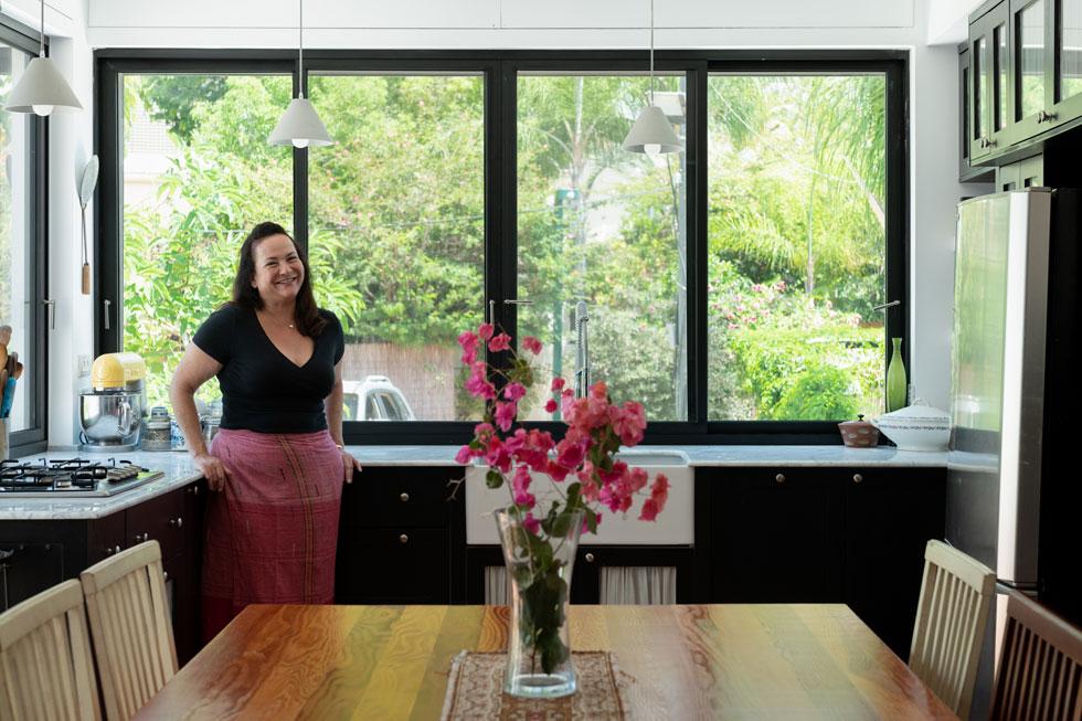 ראמי-כהן במטבח, על רקע השולחן הגדול, שכל הדירה תוכננה סביבו. ''זה מה שעושה לדעתי בית אמיתי של משפחה'' (צילום: גדעון לוין)