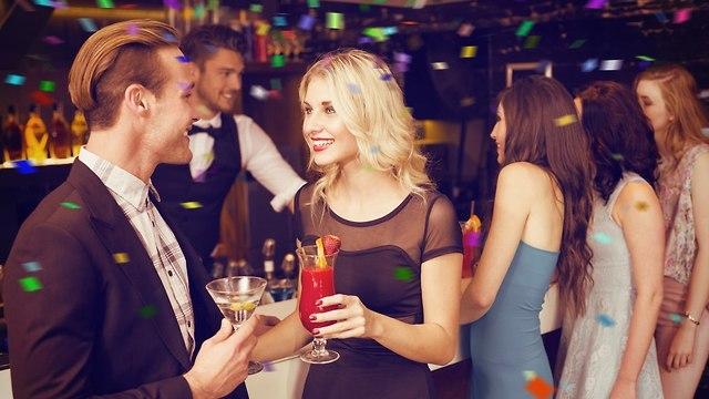 אישה מפלרטטת בבר הומה אנשים (צילום: Shutterstock)