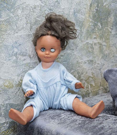"""""""היא הניצחון שלי, מזכירה לי תמיד מהיכן הגעתי"""". הבובה כרמלה על הספה בסלון (צילום: ענבל מרמרי)"""