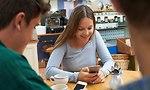 אישה בבית קפה מסתכלת על הטלפון (צילום: Shutterstock)