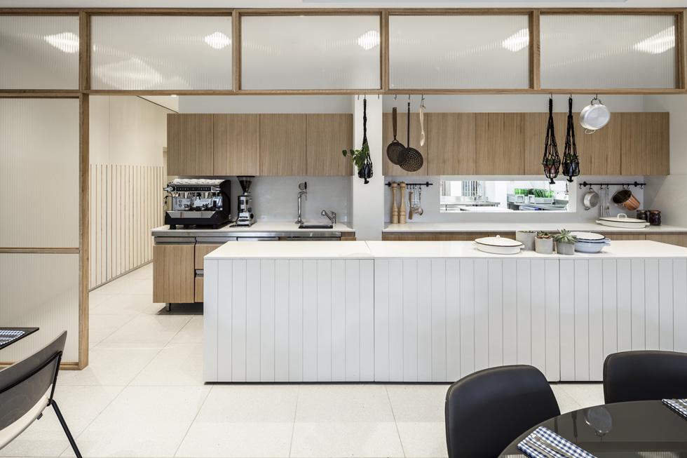 מסגרת מעץ וזכוכית מבליטה את המטבח הפתוח, המיועד להגשה, ומסתירה את הכניסות לאזור התפעולי, הכולל מטבח נוסף (צילום: עמית גרון)