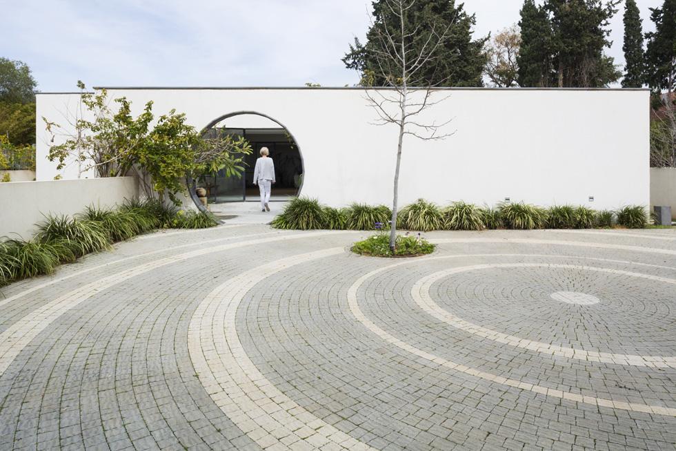 הרחבה המובילה ל''מרכז מורגנשטרן בדרך השדות'' שבכפר שמריהו רוצפה בדוגמה מעגלית ומסתיימת בקיר שבמרכזו פתח עגול (צילום: מיקאלה בורסטו)