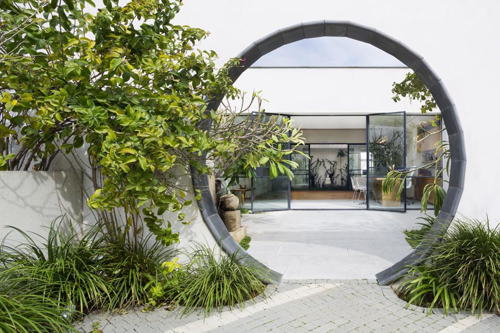 הפתח העגול עוצב בהשראת ''שער ירח'' - מרכיב אדריכלי מסורתי בחומת הגן הסיני. הוא מוסגר באבן בזלת ומוביל לחצר פנימית (צילום: מיקאלה בורסטו)