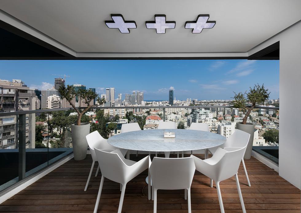 במרפסת הונח דק, ובמרכזה פינת ישיבה נוספת. ''אפשר להסתכל על הדירה כעמוסה, אך היא מוגדרת. לכל אזור יש תפקיד, והוא תוכנן לפי הצרכים'' (צילום: אלעד גונן)